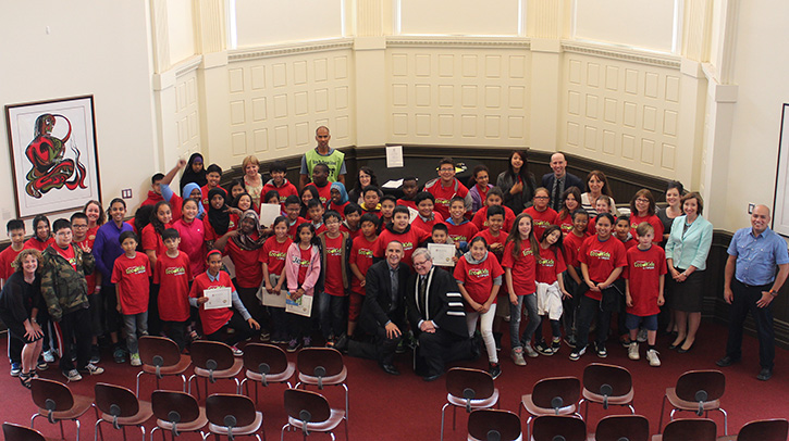 Science Kids on Campus participants gather around Minister of Children and Youth Opportunities Kevin Chief, and UWinnipeg President and Vice-Chancellor Dr. Lloyd Axworthy