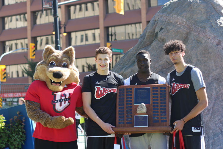 Team Wesmen Men's Basketball poses with Wes Lee Coyote and the Great Rock Climb trophy, ©UWinnipeg
