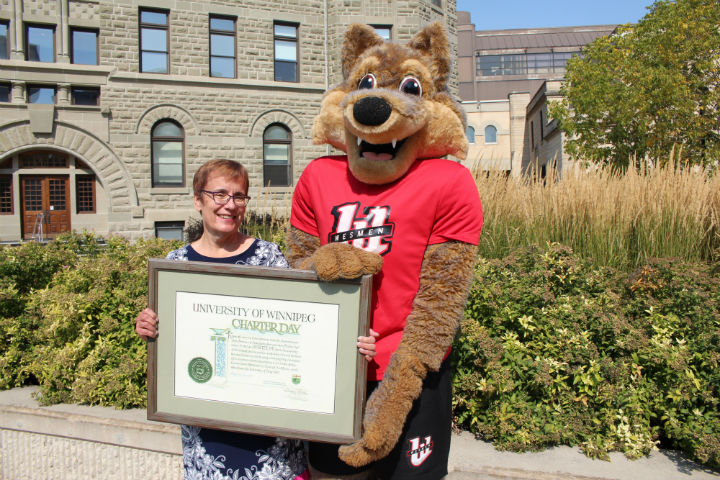 Photo: Dr. Annette Trimbee, President and Vice-Chancellor, and mascot Wes Lee hold the original Charter signed by Premier Duff Roblin on September 15, 1967 – staff photo
