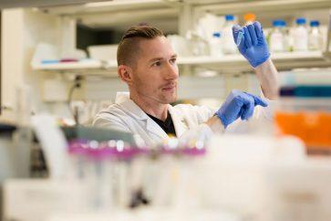 Dean Reddick examines a vial a lab, © Cory Aronec Photography