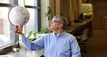 Dr. Christopher Storie holding globe