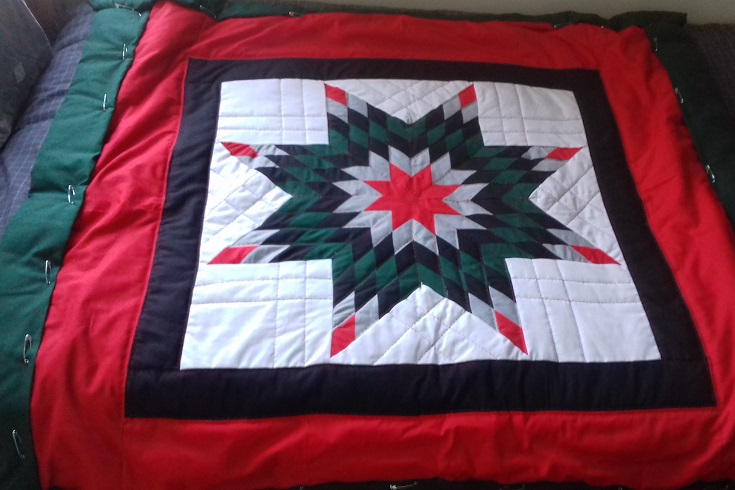 """Going around the whole quilt, at the very edge of the red fabric, baste (longer stitches) all layers together,"" advised McCluskey as she and Wolff emailed photos and instruction back and forth (photo supplied)."