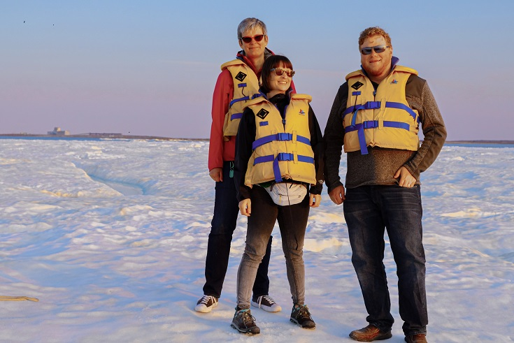 three researchers standing on ice, wearing lifejackets.