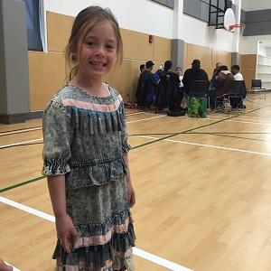 girl smiling wearing a jingle dress