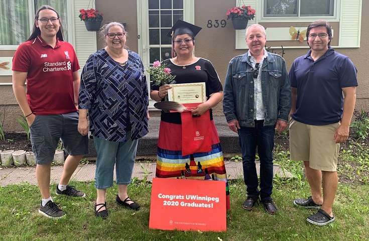graduate holding certificate, surrounded by ASSC staff.