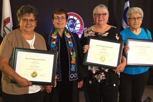 three women posing with President Trimbee holding honorary doctorates