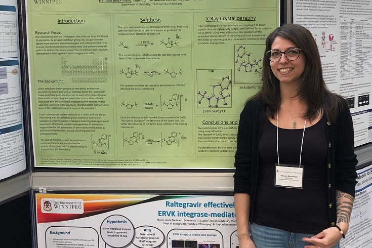 student in front of science poster